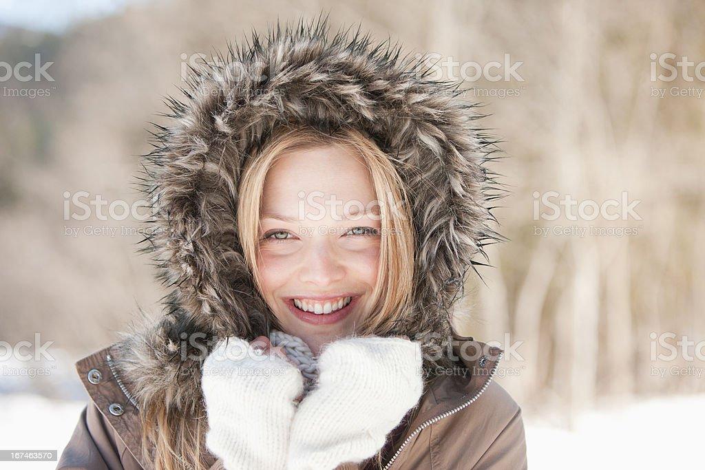 Portrait of smiling woman wearing fur hood coat stock photo