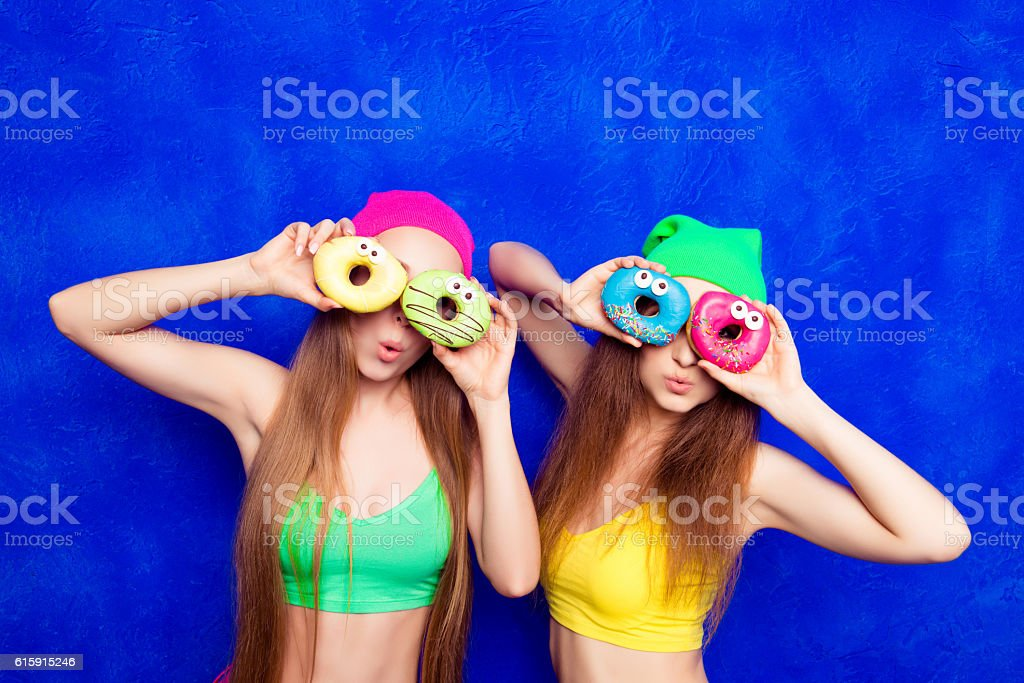 Portrait of  smiling women covering eyes with donuts stock photo