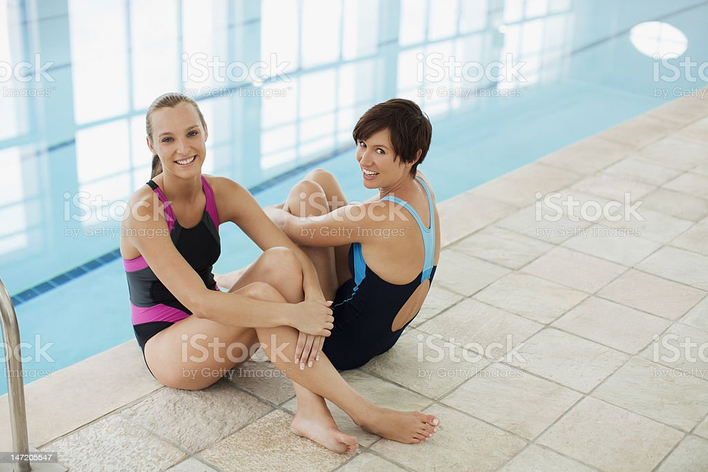 Portrait of smiling women in bathing suits at poolside royalty-free stock photo