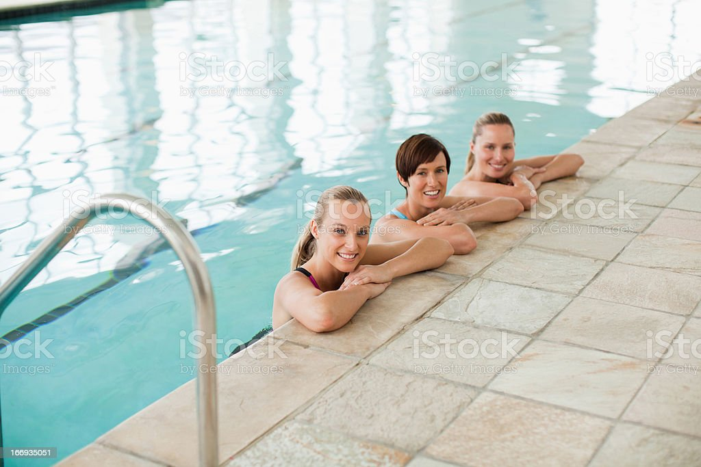 Portrait of smiling women leaning on edge of swimming pool royalty-free stock photo