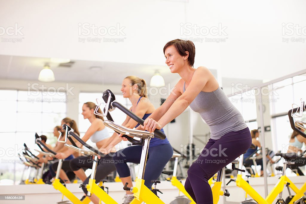 Portrait of smiling women on exercise bikes in gymnasium stock photo
