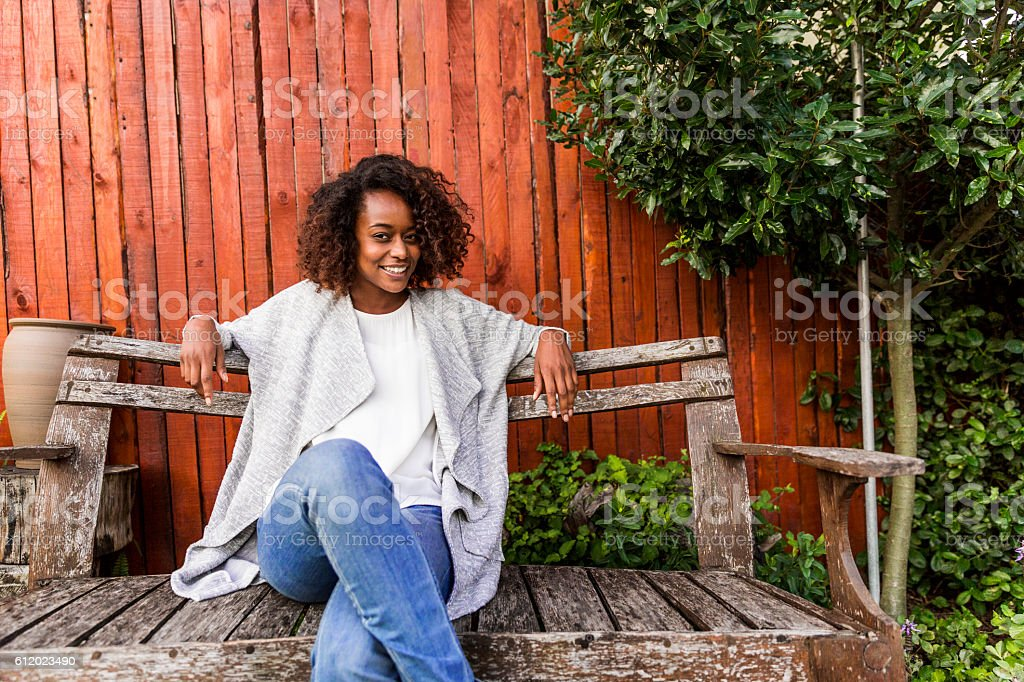 Portrait of smiling women sitting on bench in yard stock photo