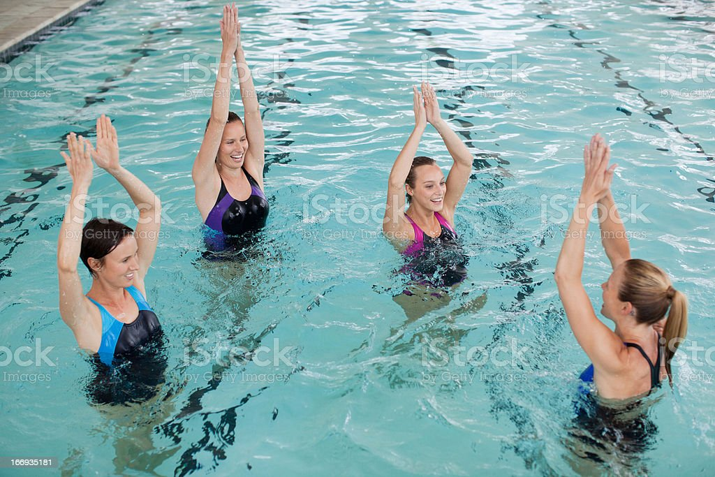 Portrait of smiling women with arms raised in swimming pool royalty-free stock photo