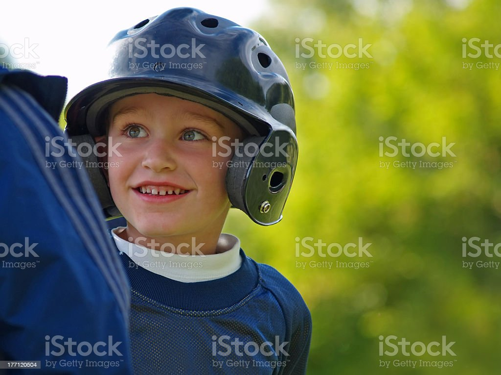 Portrait of smiling young boy with a helmet playing baseball stock photo