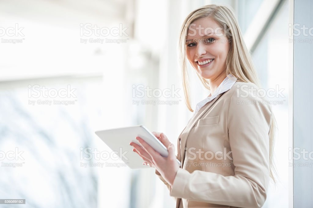 Portrait of smiling young businesswoman using digital tablet in office stock photo