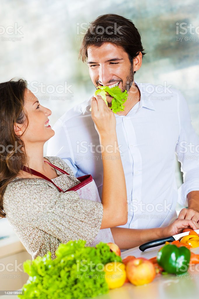 Portrait of smiling young couple preparing lunch together. royalty-free stock photo