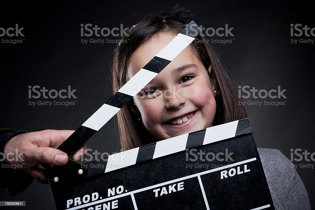 Portrait of smiling young girl behind a movie clapper board stock photo