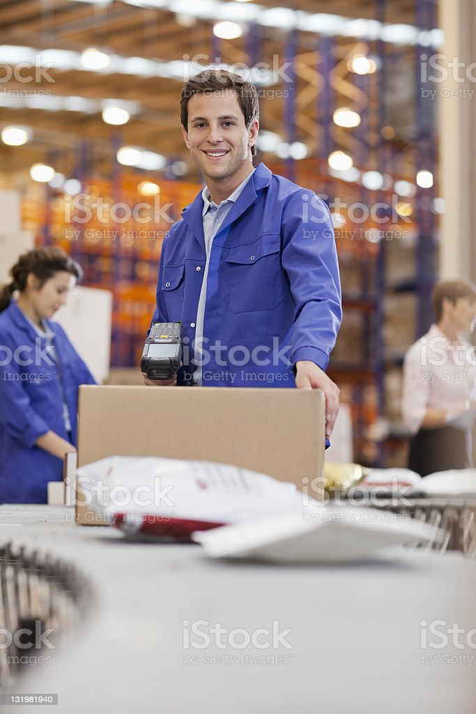 Portrait of smiling young male warehouse worker with colleagues in background stock photo