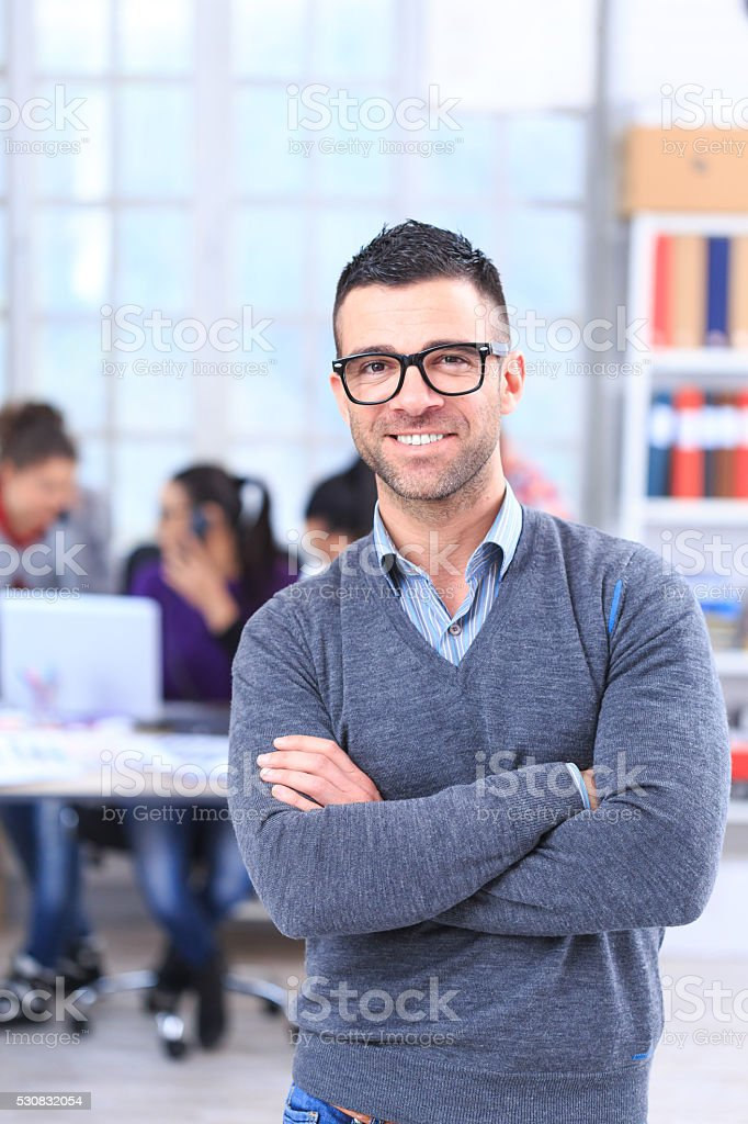 Portrait of smiling young man at the office-vertical stock photo