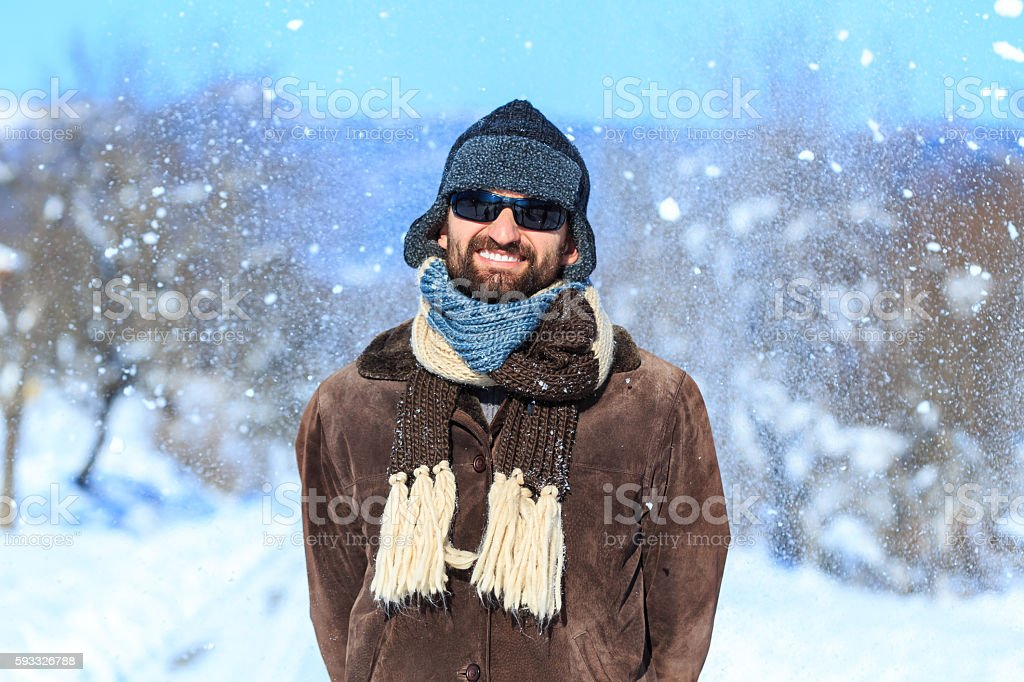 Portrait of smiling young man having fun on snow mountain stock photo