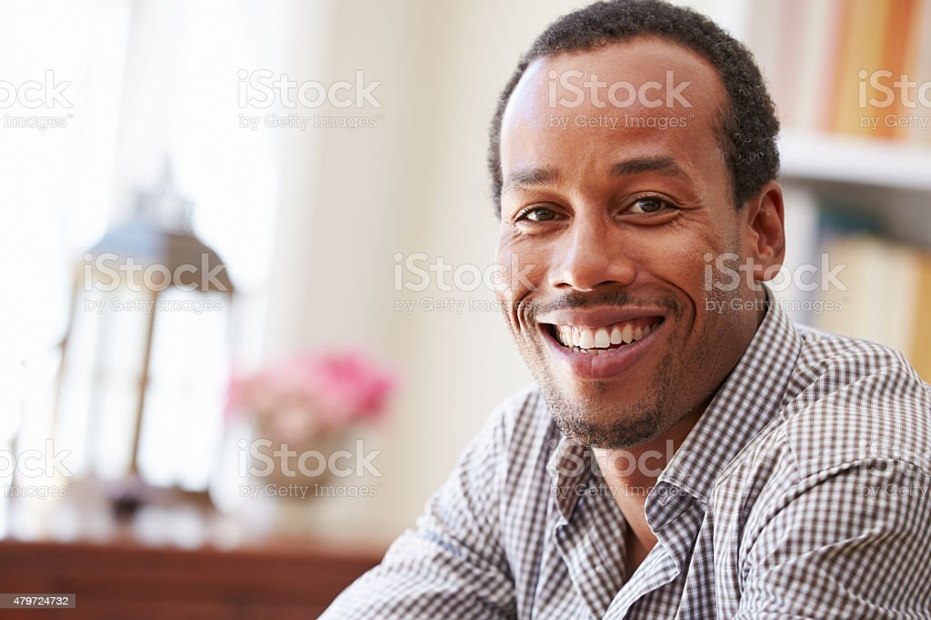 Portrait of smiling young man sitting in a room stock photo