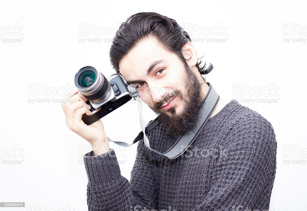 Portrait of smiling young photographer over white background stock photo