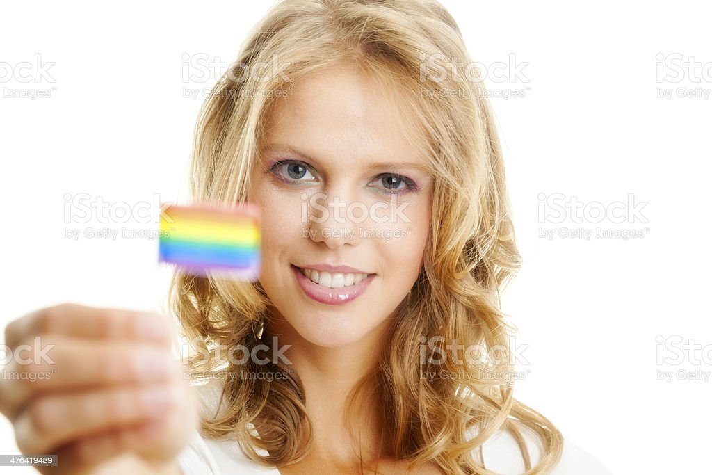 Portrait of smiling young woman holding a small rainbow flag. royalty-free stock photo
