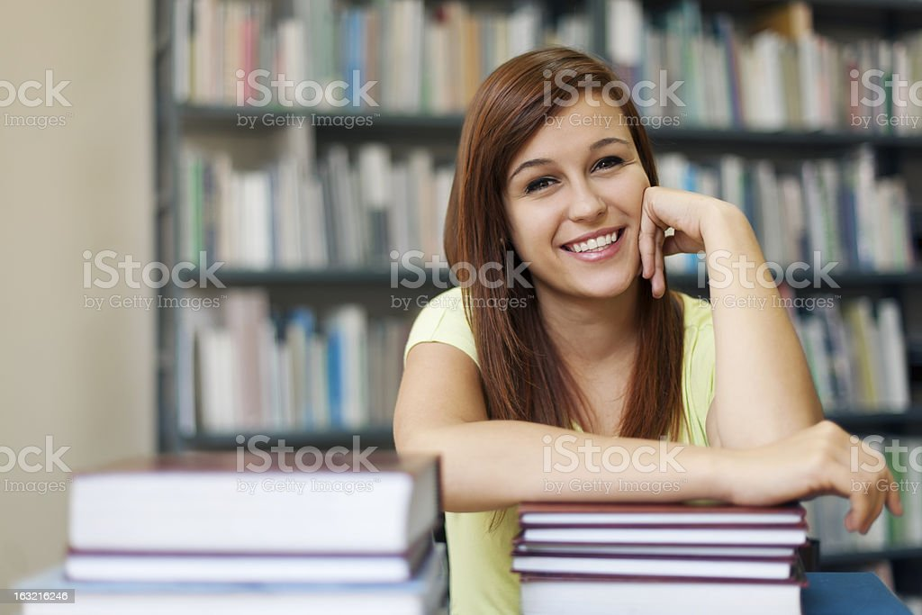 Portrait of young student woman in library stock photo