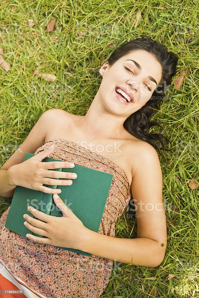 Portrait of smiling young woman lying on grass royalty-free stock photo