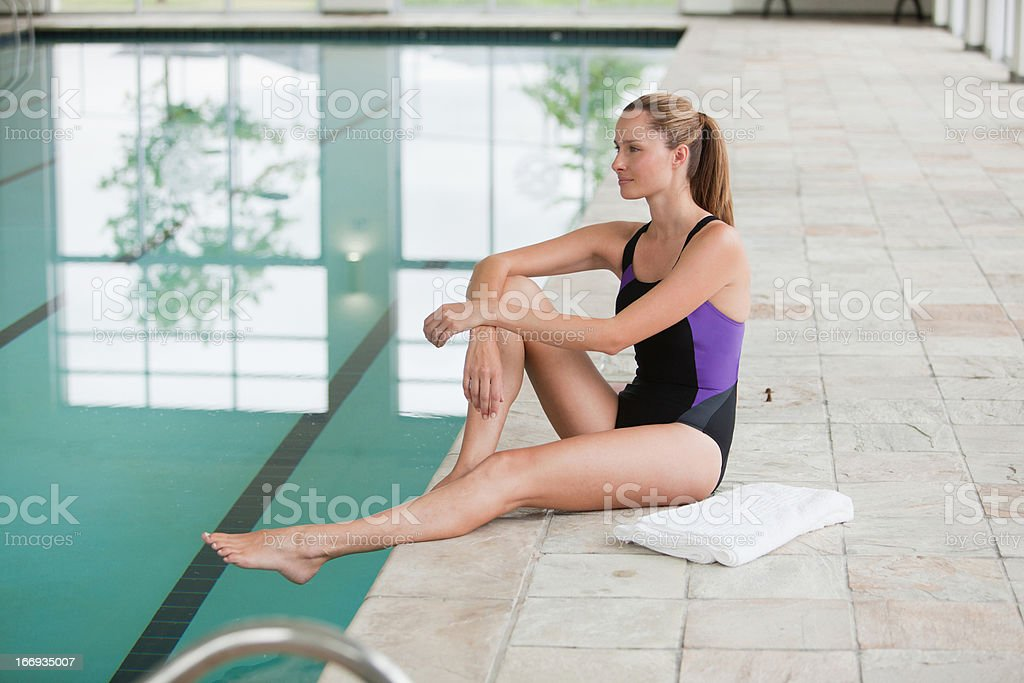Portrait of smiling young woman sitting at edge of swimming pool royalty-free stock photo