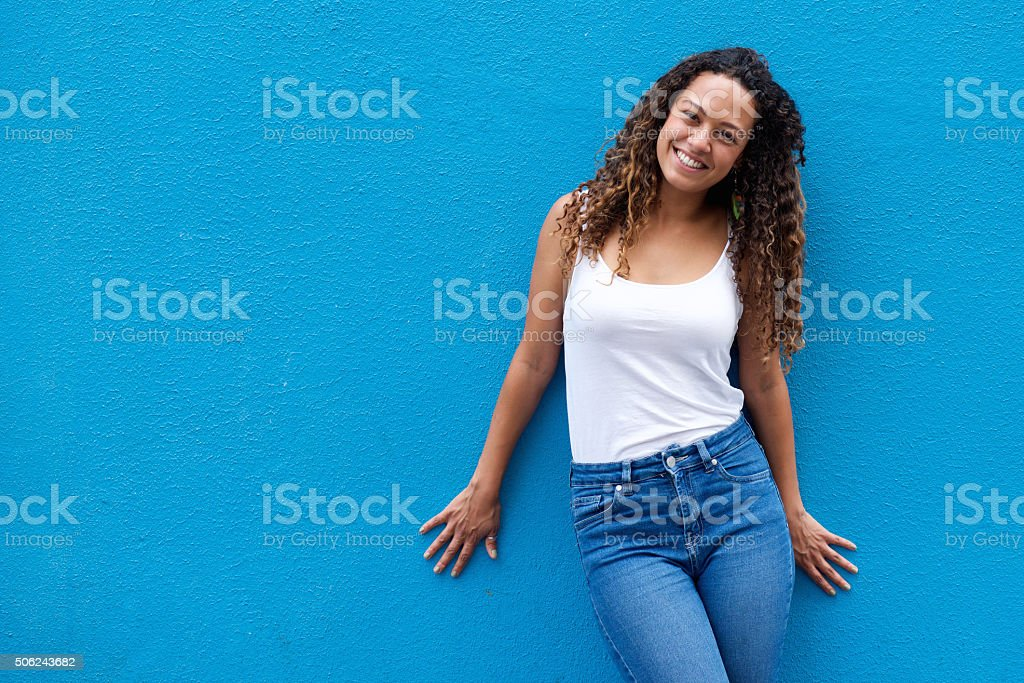 Portrait of smiling young woman standing against blue wall stock photo
