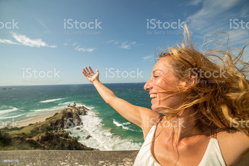 Portrait of smiling young woman with blowing hair at seaside stock photo