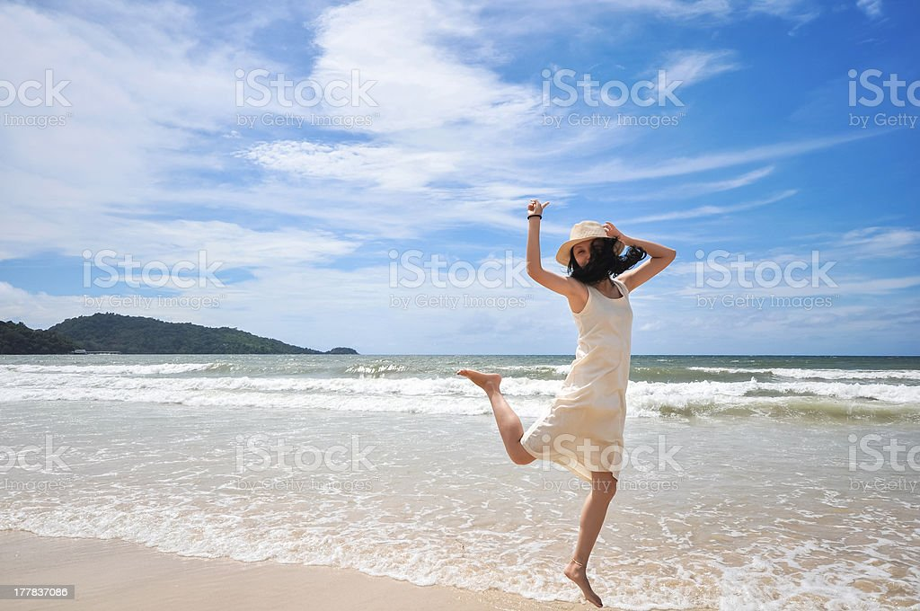 portrait of smilling young beautiful woman jumping on the beach royalty-free stock photo