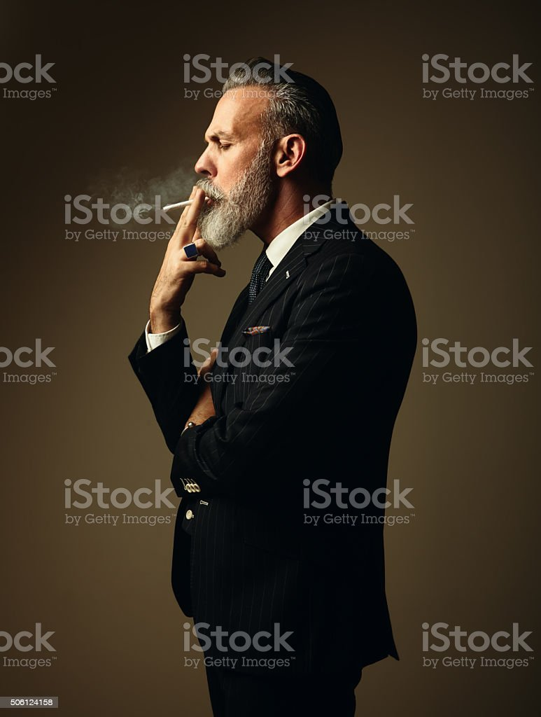 Portrait of smoking gentleman wearing trendy suit and stands against stock photo