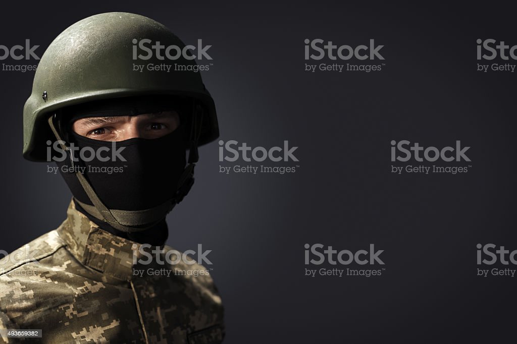 Portrait of soldier on dark background with space for text stock photo