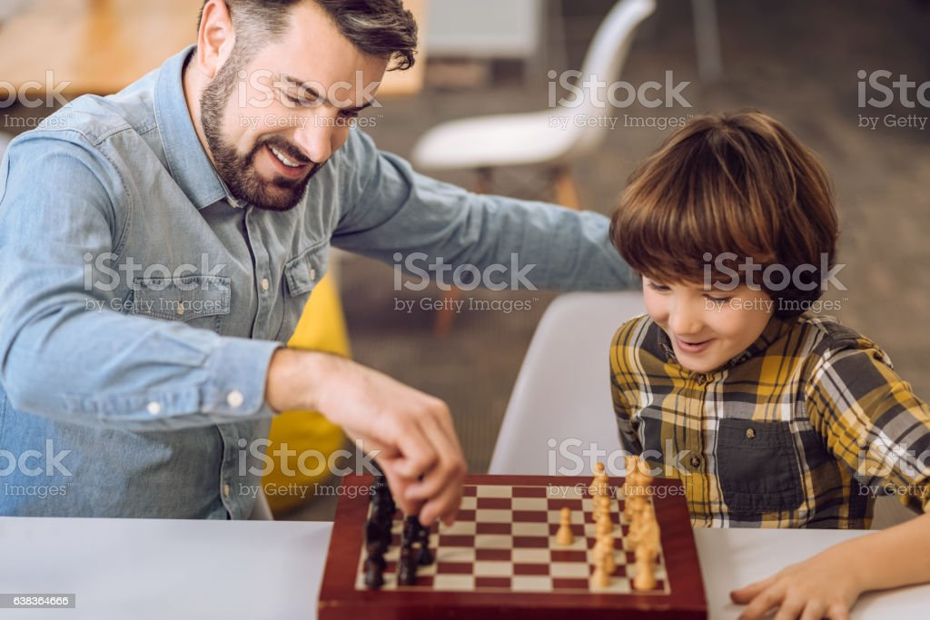 Portrait of son and father while playing chess stock photo