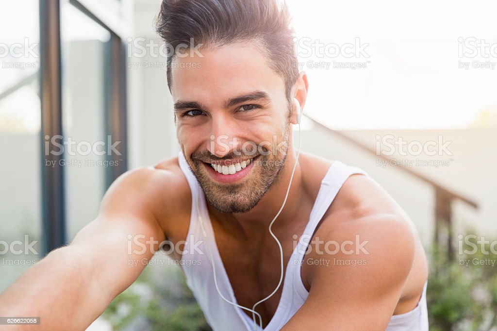 Portrait of sporty young man smiling in backyard stock photo