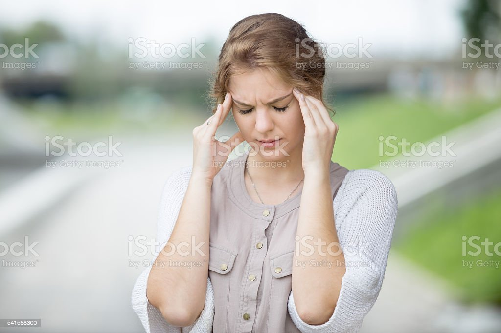 Portrait of stressed woman with headache outdoors stock photo