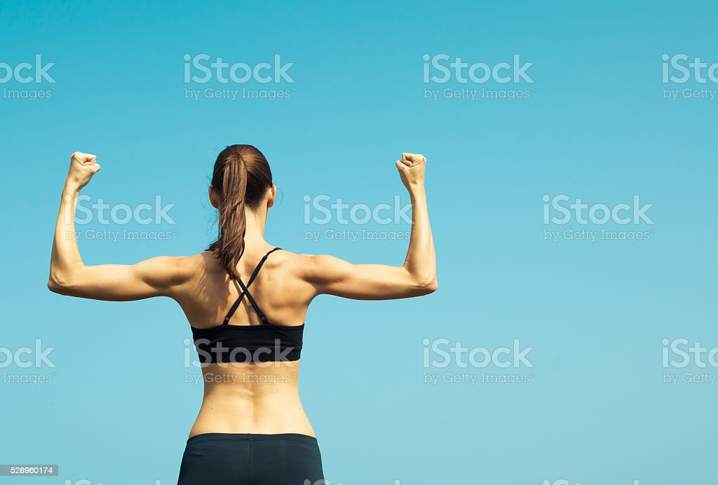 Portrait of strong female flexing. stock photo
