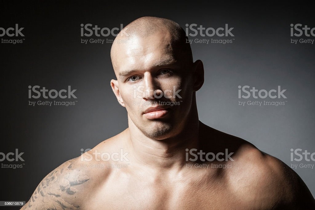 portrait of strong man isolated on dark background stock photo