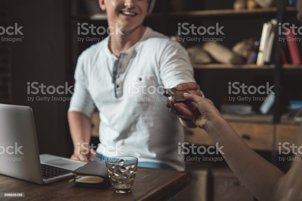 Portrait of stylish man paying with credit card in coffee shop stock photo