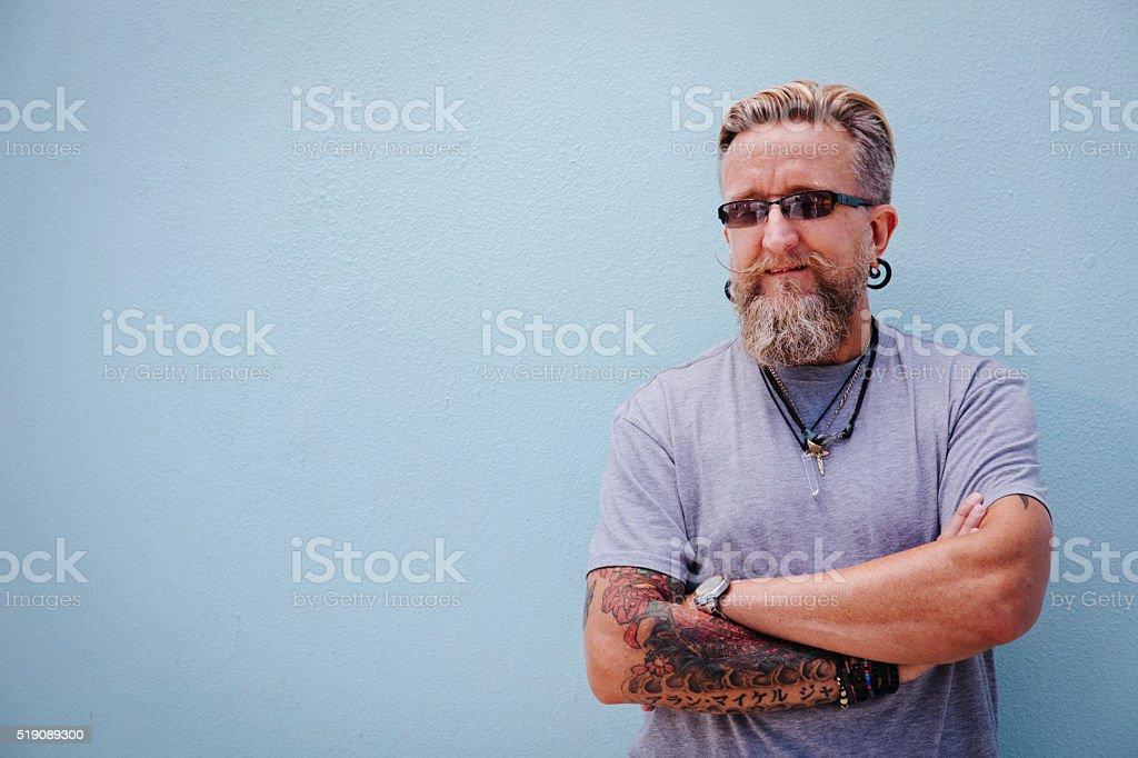 Portrait of stylish mature man with beard and tattoo stock photo
