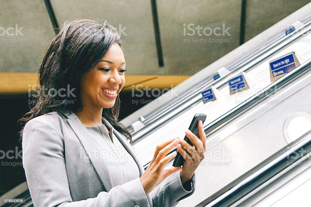 Portrait Of Successful Businesswoman Using Smartphone On Subway Escalators stock photo