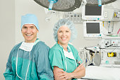 Portrait of surgeon and nurse together in hospital operating room