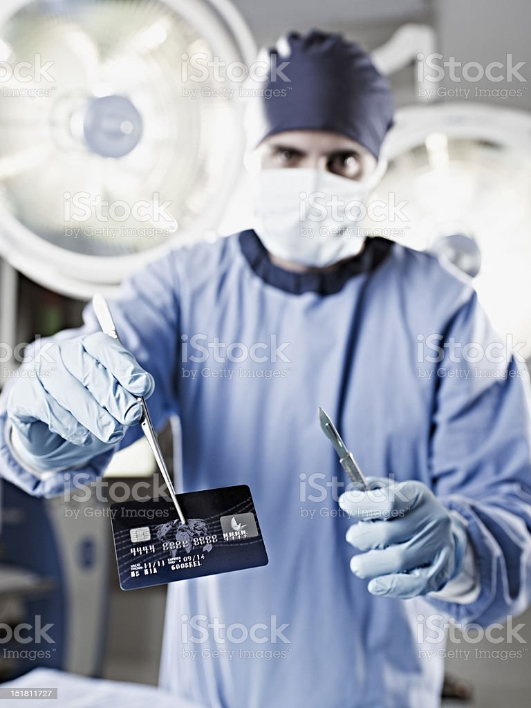 Portrait of surgeon holding credit card in surgery royalty-free stock photo
