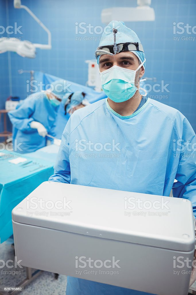 Portrait of surgeon holding ice box while colleagues performing operation stock photo