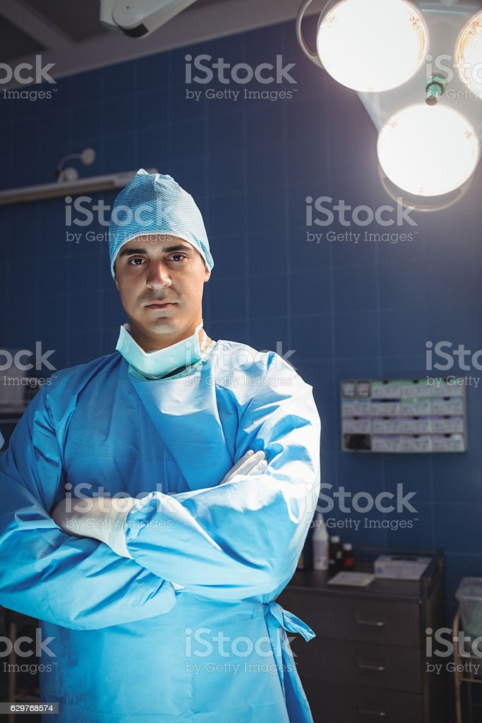 Portrait of surgeon standing with arms crossed in operation room stock photo