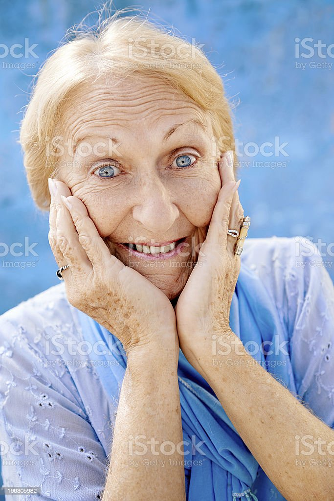 Portrait of surprised senior woman with hands on face royalty-free stock photo
