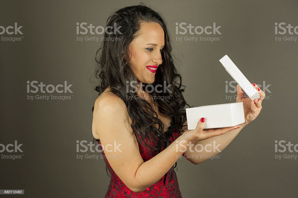 Portrait of surprised woman opening a present box stock photo