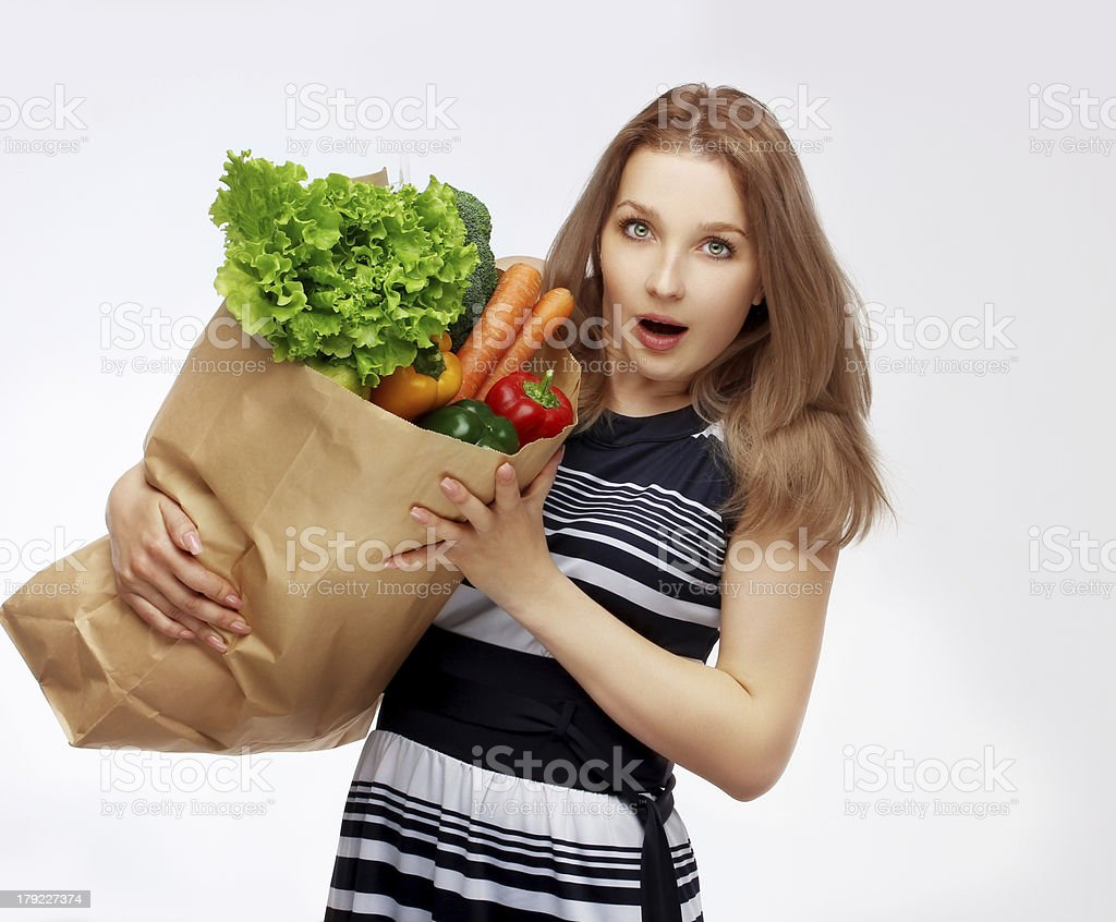 Portrait of surprised young beautiful woman  holding grocery shopping bag royalty-free stock photo