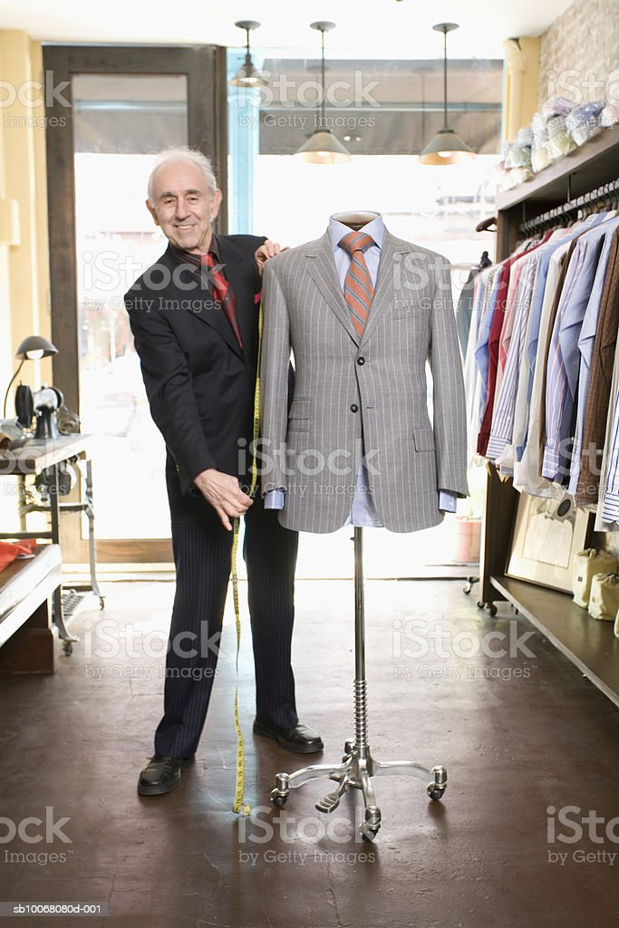 Portrait of tailor by dressmaker's model in store stock photo