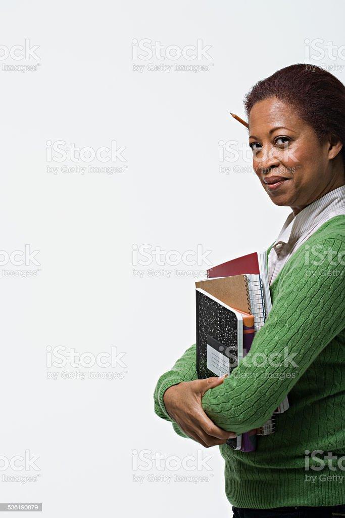 Portrait of teacher holding books stock photo