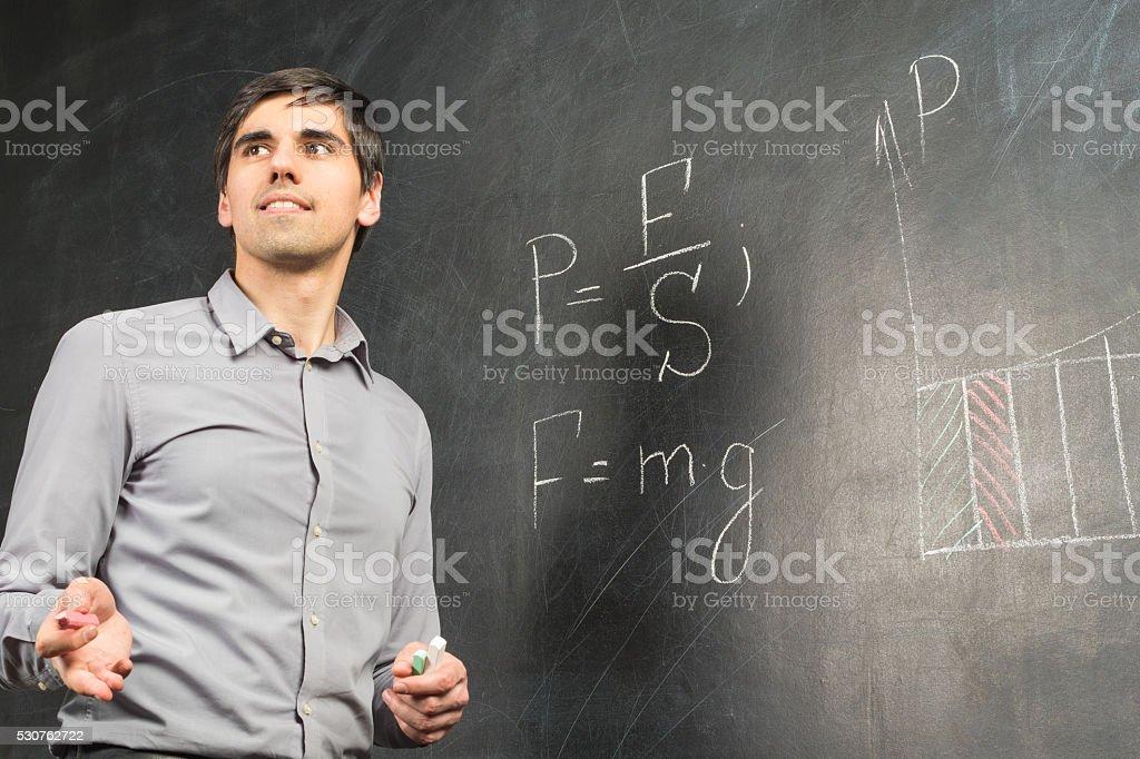 Portrait of teacher man near chalkboard speaking to audience stock photo