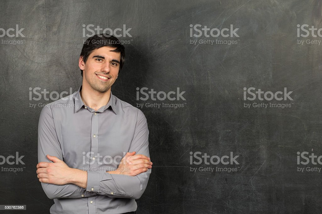 Portrait of teacher man standing near chalkboard background stock photo