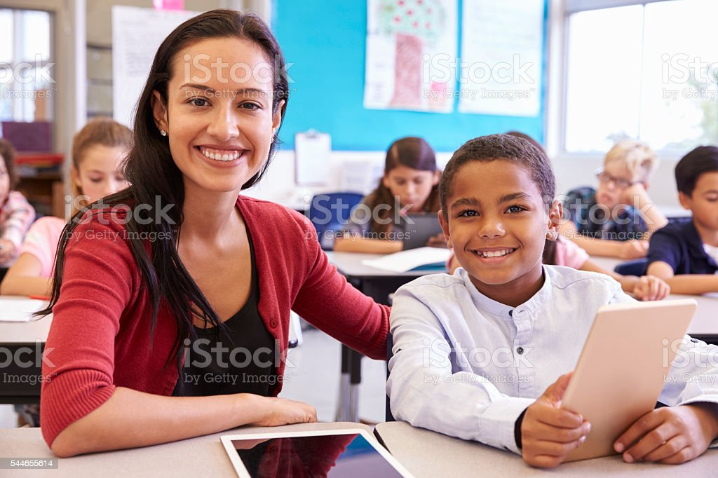Portrait of teacher with elementary school boy at his desk stock photo