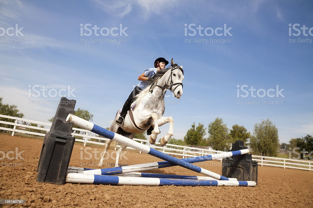 Portrait of teenage girl jumping on a horse royalty-free stock photo