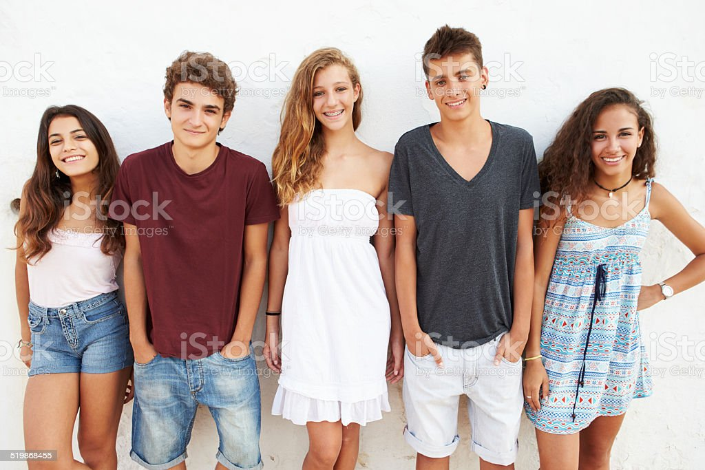 Portrait Of Teenage Group Leaning Against Wall stock photo