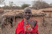 Portrait of teenage Maasai girl in traditional dress outside hut.