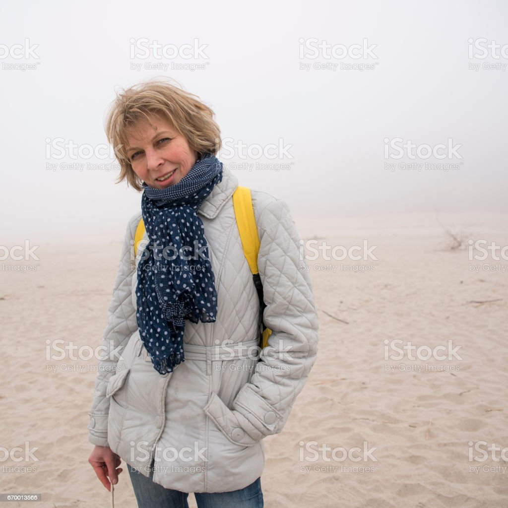 Portrait of the attractive, cheerful mature 50-years-old woman on the beach stock photo