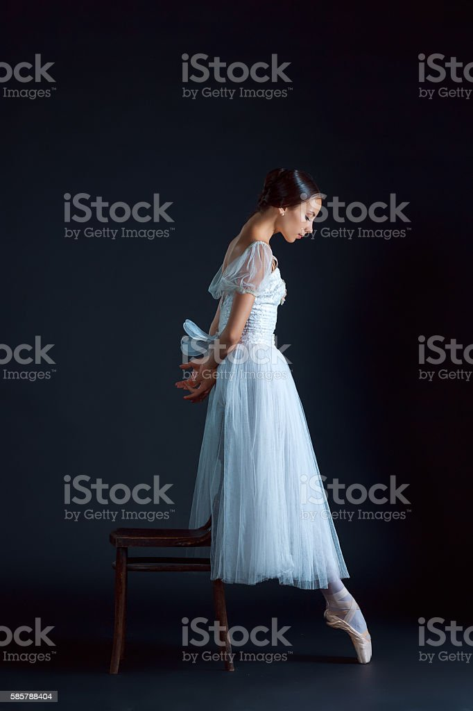 Portrait of the classical ballerina in white dress on black stock photo